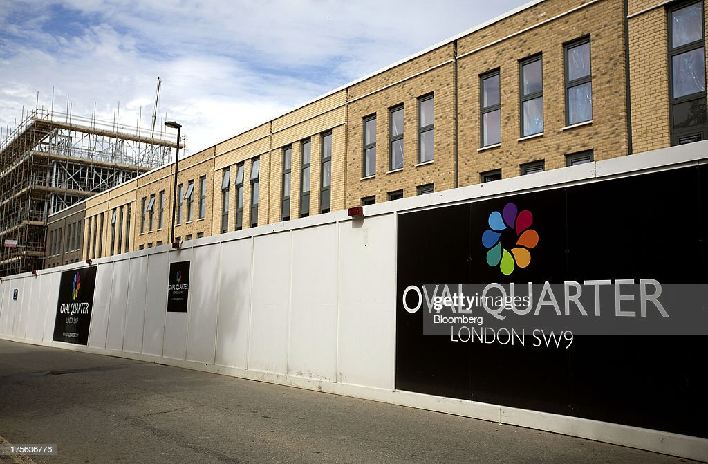 Hoardings stand outside the Oval Quarter, a shared ownership, private and social residential housing complex developed by Higgins Group Plc in partnership with Nottinghill Housing and Pinnacle Regeneration Group, in London, U.K., on Monday, Aug. 5, 2013. U.K. house prices rose 0.8 percent in July, from 0.3 percent the previous month, Nationwide Building Society said. Photographer: Simon Dawson/Bloomberg via Getty Images