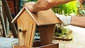Close up on a man building wooden bird feeder in garden.