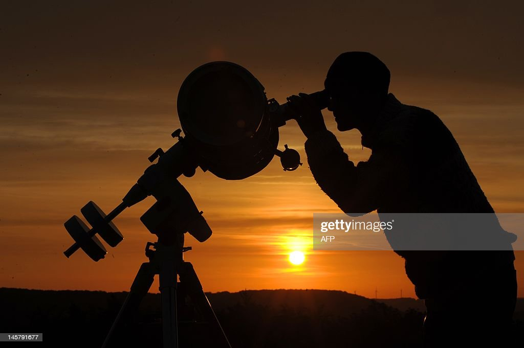 A hobby astronomer points his telescope at the yello disk of the rising sun as he observes the transit of planet Venus in Ziegenhain near Jena, eastern Germany, on June 6, 2012. The event, only to be seen again in 105 years, began shortly after 2200 GMT on Tuesday, visible first from the Pacific and north and central Americas as a small black dot trailing across the solar surface. AFP PHOTO / ANGELIKA WARMUTH GERMANY OUT
