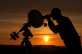 A hobby astronomer points his telescope at the yello disk of the rising sun as he observes the transit of planet Venus in Ziegenhain near Jena...