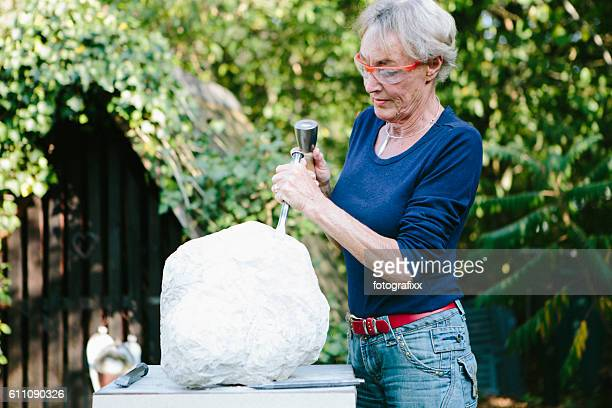 Hobby: senior woman works with a chisel at her sculpture