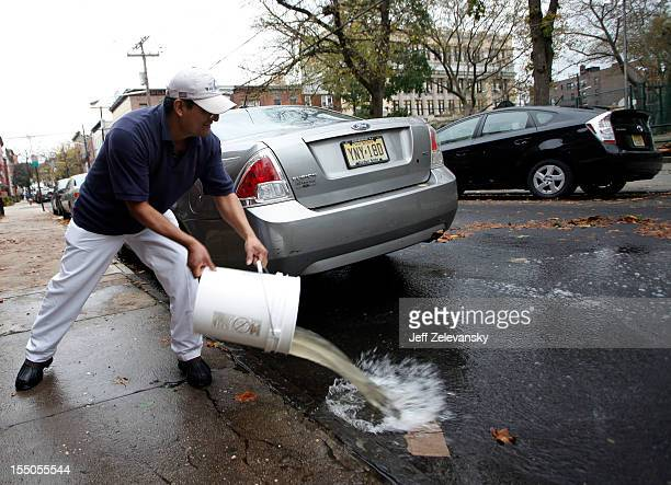 Hoboken resident employs a bucket brigade to clear water from a ground floor apartment on Fifth Street on October 31 2012 in Hoboken New Jersey Known...