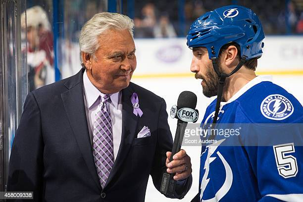 Hockey analyst Bobby Taylor wears purple in recognition of Hockey Fights Cancer night while interviewing Jason Garrison of the Tampa Bay Lightning...