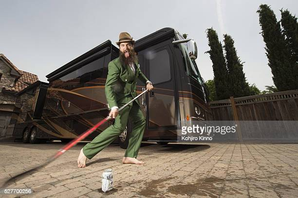 Casual portrait of San Jose Sharks defenseman Brent Burns striking beer can with hockey stick in front of his 441/2 foot RV during photo shoot...