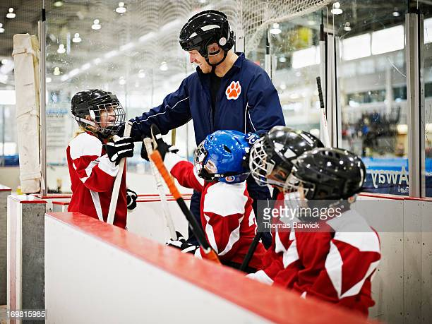 Hockey coach congratulating young female player