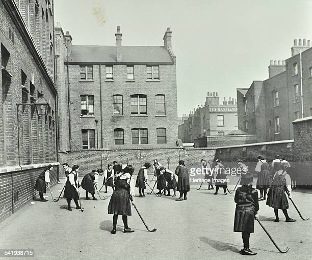 Hockey game Myrdle Street Girls School Stepney London 1908 Girls about to begin a game of hockey in the school playground The playground is...
