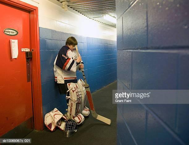 Hockey goalie (14-15) in locker room hallway