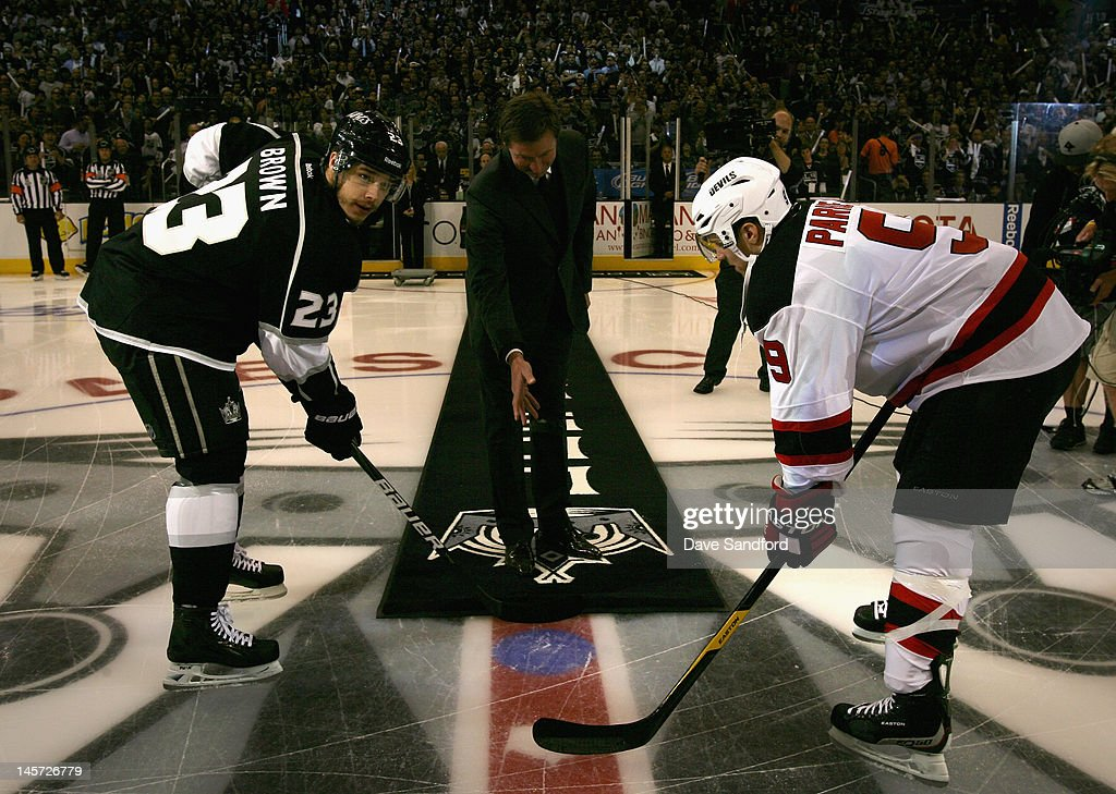 Hockey great Wayne Gretzky (C) drops the ceremonial first puck with Zach Parise #9 of the New Jersey Devils (R) and Dustin Brown #23 of the Los Angeles Kings (L) before Game Three of the 2012 Stanley Cup Final at the Staples Center on June 4, 2012 in Los Angeles, California.