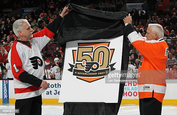 Hockey Hall of Fame member Bernie Parent and longtime Philadelphia Flyers season ticket holder Joe Sahina unveil a logo that the Flyers will use...