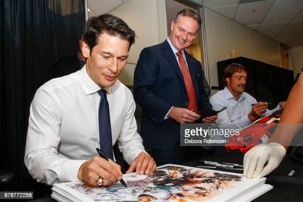 Hockey Hall of Famers and former Anaheim Ducks Paul Kariya left and Teemu Selanne right sign autographs as Ducks Broadcaster Brian Hayward talks with...