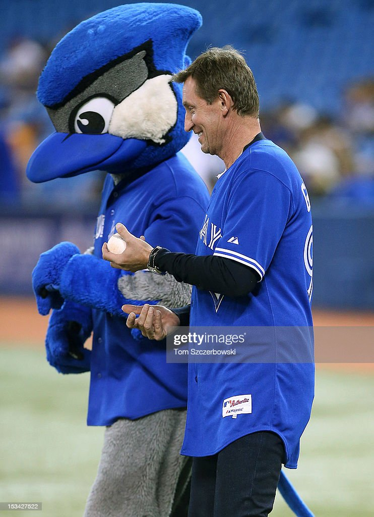 Hockey legend Wayne Gretzky goes to throw out the first pitch with Toronto Blue Jays mascot Ace before the start of the MLB game against the Minnesota Twins on October 1, 2012 at Rogers Centre in Toronto, Ontario, Canada.