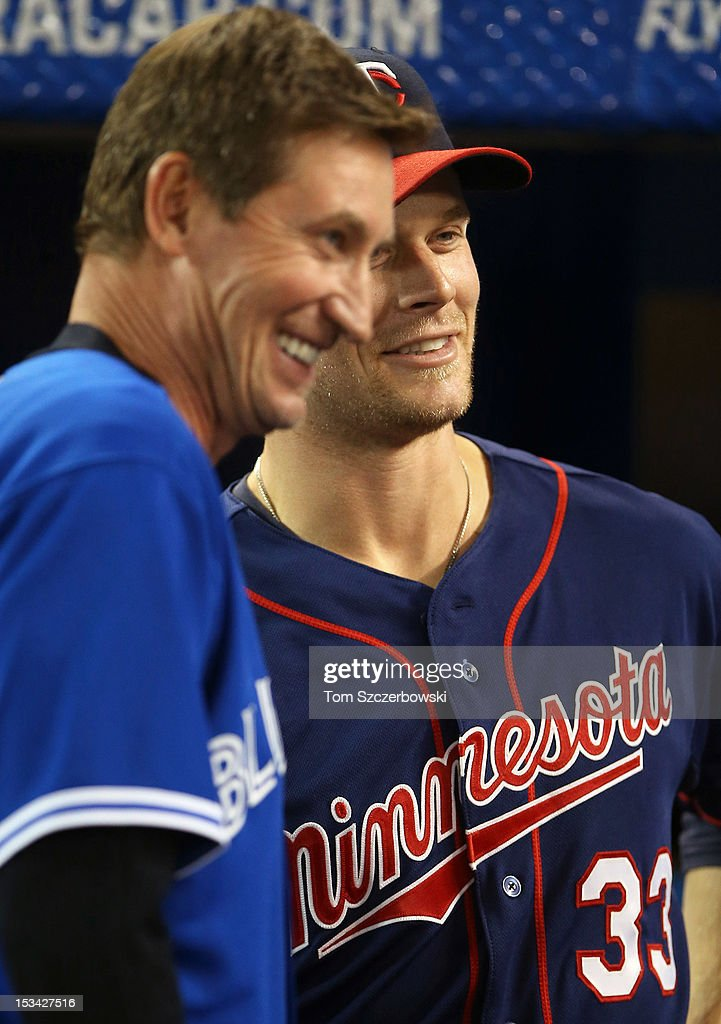 Hockey legend Wayne Gretzky meets with Canadian player Justin Morneau #33 of the Minnesota Twins before their MLB game against the Toronto Blue Jays on October 1, 2012 at Rogers Centre in Toronto, Ontario, Canada.