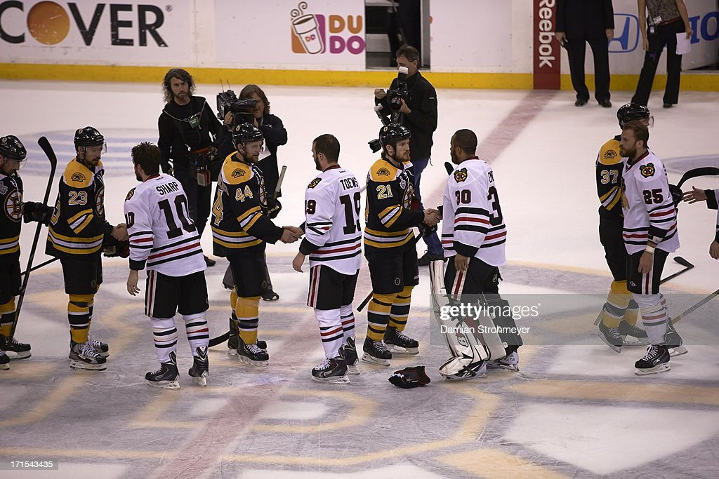 Chicago Blackhawks Patrick Sharp (10), Jonathan Toews (19), and goalie Ray Emery (30) victorious, shaking hands after winning Game 6 and championship vs Boston Bruins Andrew Ference (21), Chris Kelly (23), and Dennis Seidenberg (44) at TD Garden. Damian Strohmeyer F40 )