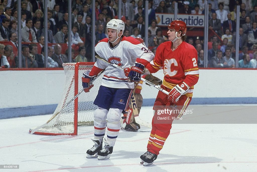 Montreal Canadiens Claude Lemieux (32) and Calgary Flames Al MacInnis (2) on ice during game. Montreal, Canada 5/16/1986--5/24/1986