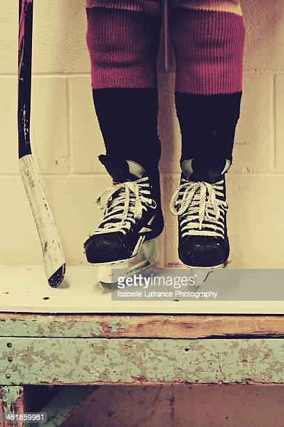 Hockey player standing on locker room bench