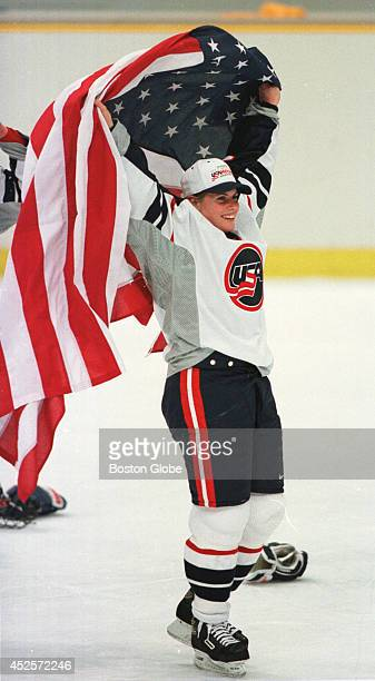 USA hockey player Tara Mounsey from Concord NH holds aloft an American flag during celebration after the US beat the Canadians 31 in women's Olympic...