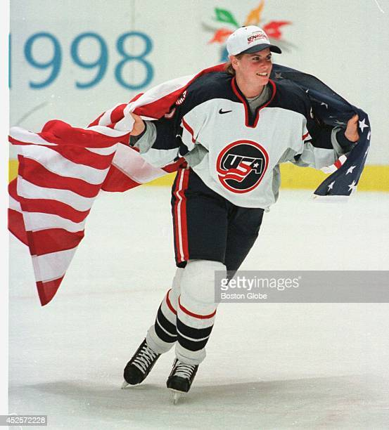 S hockey player Tara Mounsey skates around the rink wearing an American flag during post game celebration after the US beat Canada to take the...