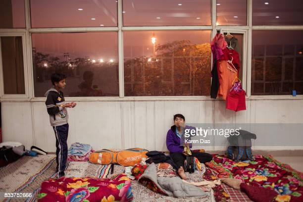 Hockey players from the Shahbad Hockey Academy share a packet of chips in a dorm room set up for students traveling from faraway towns to participate...