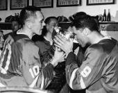 Hockey players George Armstrong Andy Bathgate and other members of the victorious Toronto Maple Leafs drink from the Stanley Cup the National Hockey...