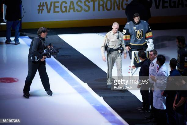 Police officer taking the ice alongside Vegas Golden Knights goalie MarcAndre Fleury during ceremony before game vs Arizona Coyotes at TMobile Arena...