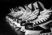 Pairs of hockey skates lined up in a locker room.