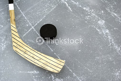 Hockey stick and black puck on ice : Stock Photo