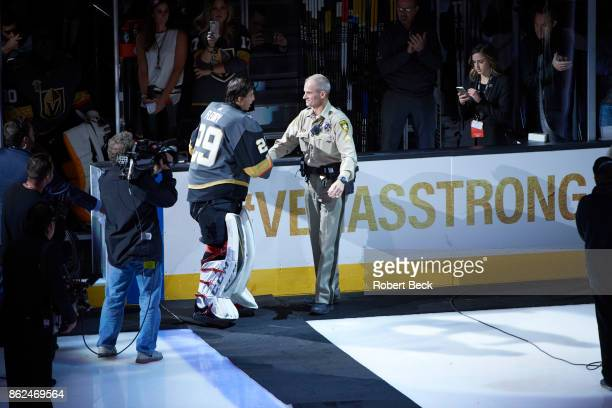 Vegas Golden Knights goalie MarcAndre Fleury shaking hands with police officer on ice during ceremony before game vs Arizona Coyotes at TMobile Arena...