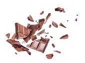 Ð¡hocolate broken into pieces in the air, isolated on a white background