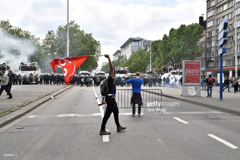 A hodded man walks and brandishes a flag of the Belagian socialist party as Belgium's riot police stand guard during a national anti-austerity demonstration on May 24, 2016, in Brussels Belgian trade unions called for mass protests against the centre-right government's proposed work reforms as they plan rallies and strikes over the next few months. / AFP / Belga / DIRK WAEM / Belgium OUT
