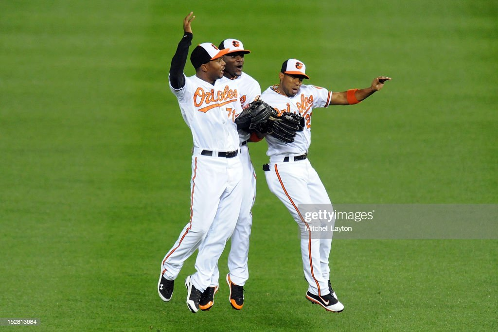 L.J. Hoes #71, Adam Jones #10 and Endy Chaves #27 of the Baltimore Orioles celebrate a win after a baseball game against the Toronto Blue Jays on September 26, 2012 at Oriole Park at Camden Yards in Baltimore, Maryland. The Orioles won 12-2.