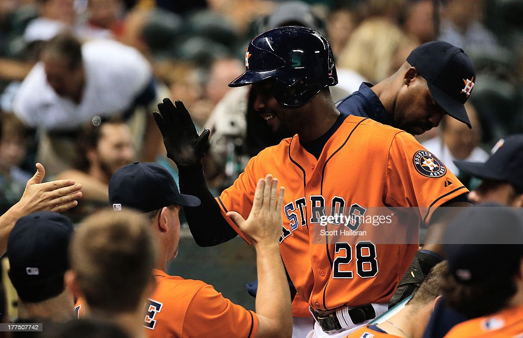 L.J. Hoes #28 of the Houston Astros celebrates in the dugout with his teammates after scoring a run in the fourth inning against the Toronto Blue Jays at Minute Maid Park on August 23, 2013 in Houston, Texas.