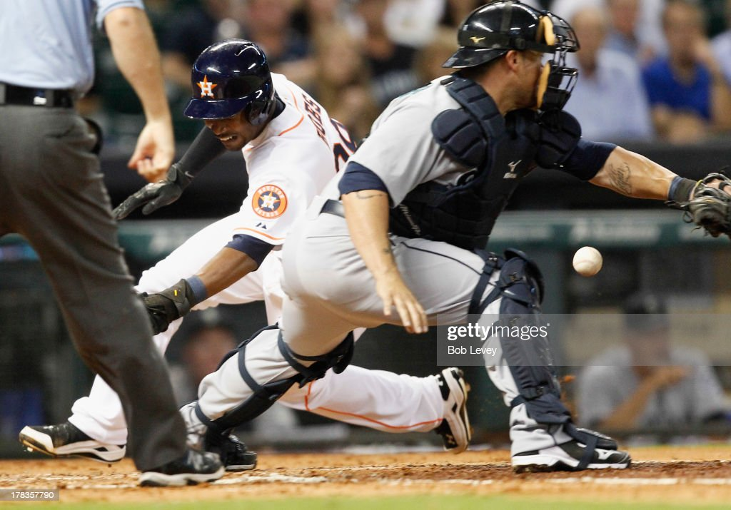 L.J. Hoes #28 of the Houston Astros slides around catcher <a gi-track='captionPersonalityLinkClicked' href=/galleries/search?phrase=Humberto+Quintero&family=editorial&specificpeople=226980 ng-click='$event.stopPropagation()'>Humberto Quintero</a> #35 of the Seattle Mariners as he scores in the fourth inning at Minute Maid Park on August 29, 2013 in Houston, Texas.