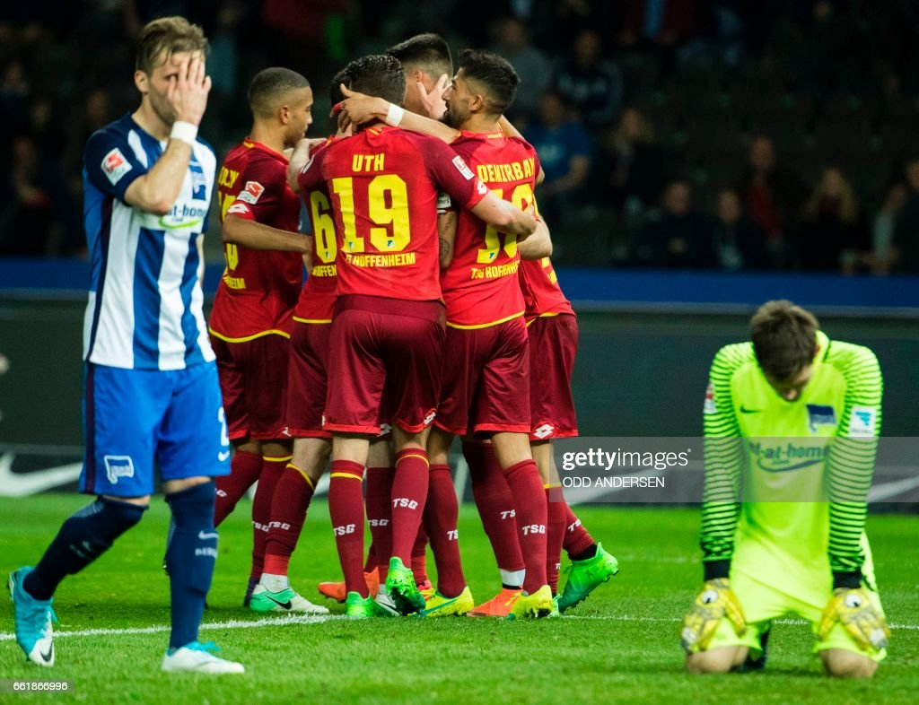 TOPSHOT - Hoffenheim players celebrate their third goal as Berlin players despair during the German First division Bundesliga football match Hertha Berlin v Hoffenheim at the Olympic Stadium in Berlin, on March 31, 2017. / AFP PHOTO / Odd