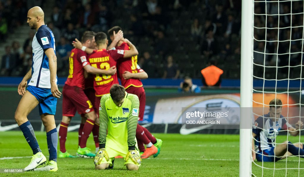 Hoffenheim players celebrate their third goal as Berlin players despair during the German First division Bundesliga football match Hertha Berlin v Hoffenheim at the Olympic Stadium in Berlin, on March 31, 2017. / AFP PHOTO / Odd