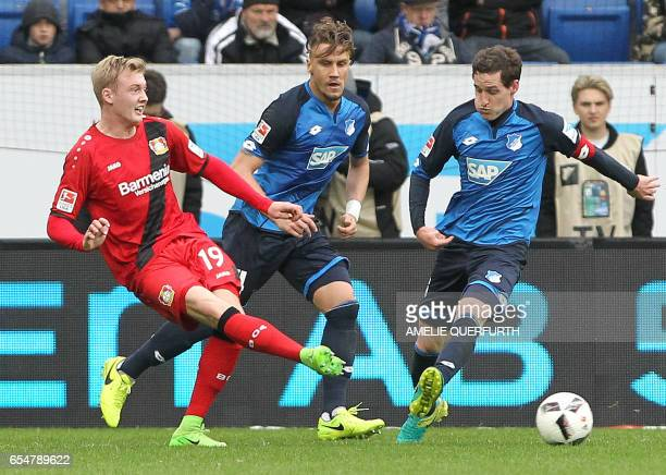 Hoffenheim's forward Mark Uth and Leverkusen's defender Jonathan Glao Tah and Leverkusen's Austrian defender Aleksandar Dragovic vie for the ball...