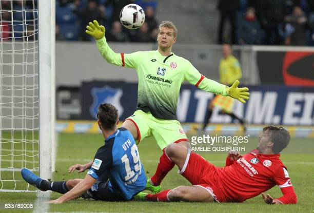 Hoffenheim's forward Mark Uth vie for the ball with Mainz' Danish goalkeeper Jonas Loessl and Mainz' Italian defender Giulio Donati during the German...