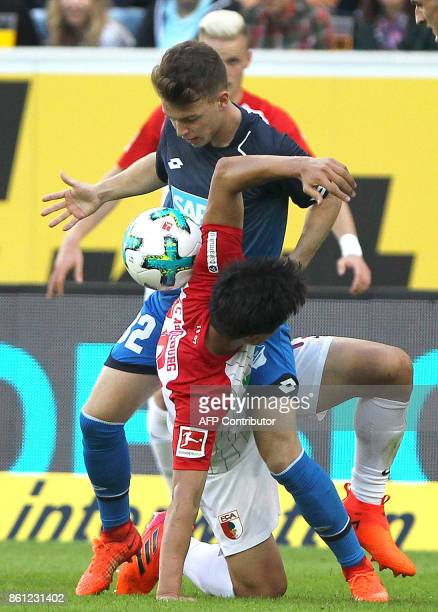 Hoffenheim's German midfielder Dennis Geiger and Augsburg's South Korean midfielder Koo Jacheol vie for the ball during the German First division...