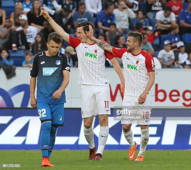 Hoffenheim's German midfielder Dennis Geiger looks on as Augsburg's German midfielder Daniel Baier congratulates Augsburg's Austrian midfielder...