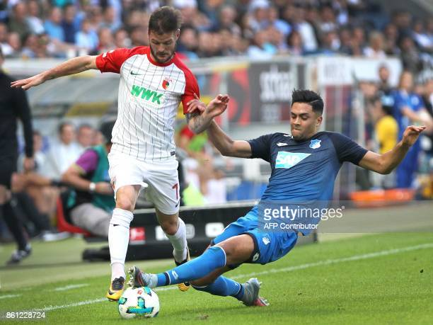 Hoffenheim's German midfielder Nadiem Amiri and Augsburg's German midfielder Marcel Heller vie for the ball during the German First division...