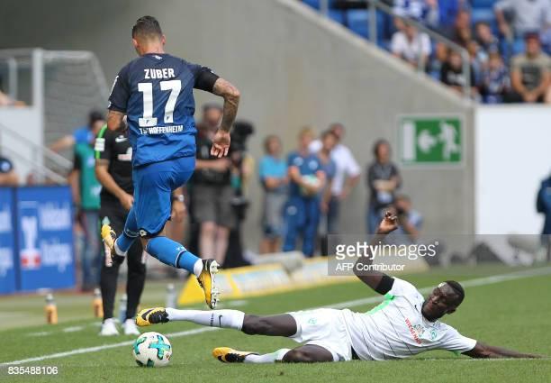 Hoffenheim's Swiss midfielder Steven Zuber and Bremen's Senegalese defender Lamine Sane vie for the ball during the German First division Bundesliga...