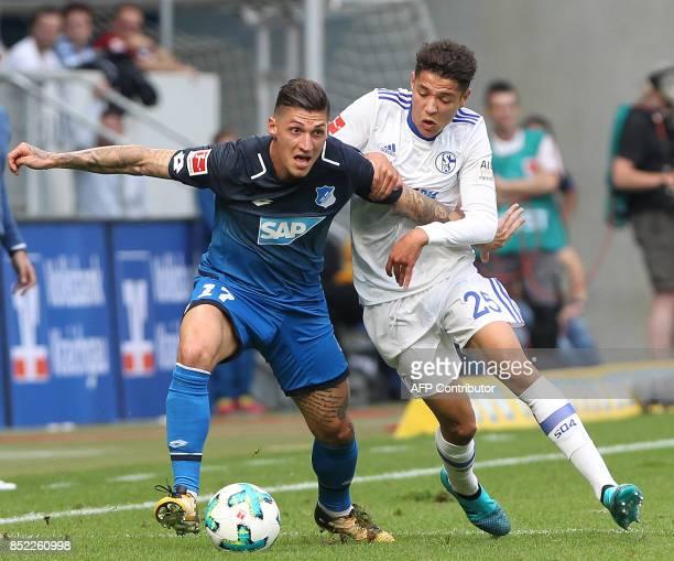 Hoffenheim's Swiss midfielder Steven Zuber and Schalke's French midfielder Amine Harit vie for the ball during the German first division Bundesliga...