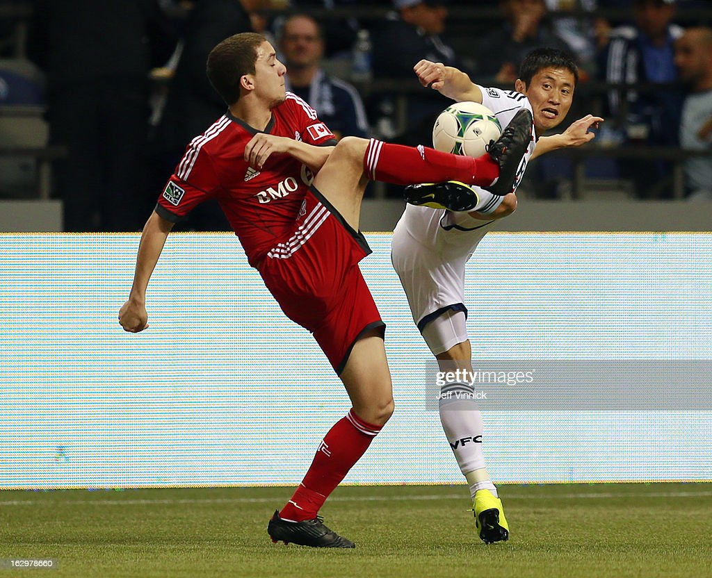 Hogan Ephraim of the Toronto FC and YoungPyo Lee of the Vancouver Whitecaps FC compete for the ball during their MLS game at BC Place March 2 2013 in...