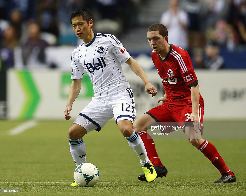 Hogan Ephraim of the Toronto FC battles YoungPyo Lee of the Vancouver Whitecaps FC for the ball during their MLS game March 2 2013 in Vancouver...