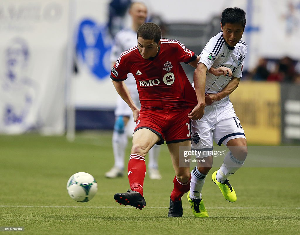 Hogan Ephraim #31 of the Toronto FC holds off Young-Pyo Lee #12 of the Vancouver Whitecaps FC while playing the ball during their MLS game March 2, 2013 at B.C. Place in Vancouver, British Columbia, Canada. Vancouver won 1-0.