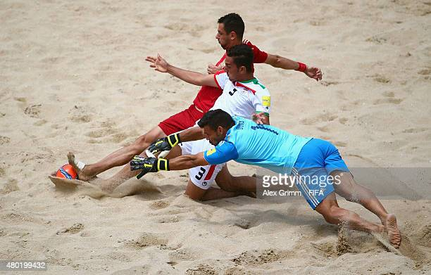 Hohammad Moradi of Iran is challenged by goalkeeper Dona and Juanma of Spain during the FIFA Beach Soccer World Cup Portugal 2015 Group C match...