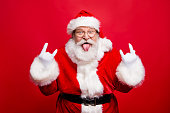Ho-ho-ho! Party time concept. Aged mature playful emotion grandfather Santa with gloves sticking tongue out and comic grimace fooling around isolated on noel bright red background