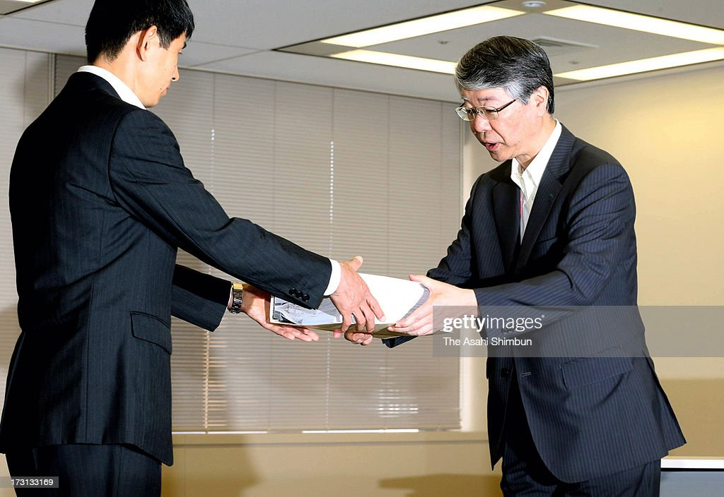 Hokkaido Electric Power Co vice president Osamu Sakai (R) hands in an application to the Nuclear Regulation Authority officer on July 8, 2013 in Tokyo, Japan. Four utilities of Hokkaido, Kansai, Shikoku and Kyushu apply for the safety examinations of ten reactors of five nuclear power plants, on the day tougher standards took effect to prevent a recurrence of the 2011 Fukushima nuclear crisis.
