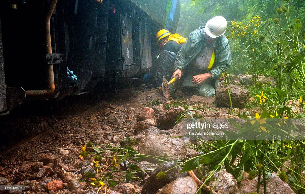 JR Hokkaido workers remove the mud on the railway track in the heavy rain on August 18, 2013 in Mori, Hokkaido, Japan. Train operation between Sapporo and Hakodate has been suspended due to a landslide triggered by a torrential rain washed the enbankment, hit 'bon' holidaymakers.