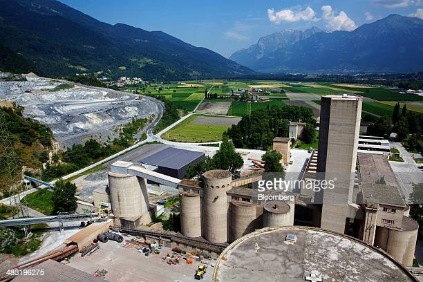 Holcim Ltd's quarry left stands on the hillside beyond the company's cement plant in Untervaz Switzerland on Wednesday July 2013 Holcim Ltd and...