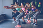 Side view of beautiful young women with perfect bodies in sportswear exercising at gym